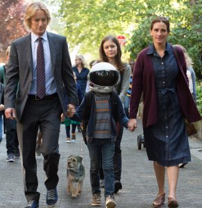 A scene from wonder the movie. Mom and Dad hold Auggies hand. Hes wearing a space helmet