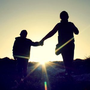 stages after diagnosis acceptance - A mother holds her sons hand. We cant see their faces as the sun is shining brightly behind them