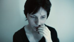 stages after diagnosis fear - A woman hold her hand to her mouth and stares down looking worried