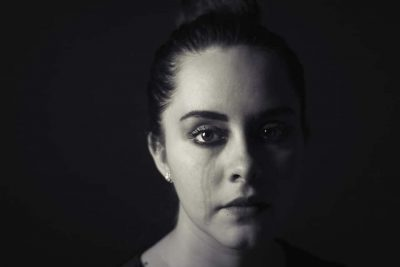stages after diagnosis grief. A woman stares at the camera with the tracks of one set of tears running down her right cheek