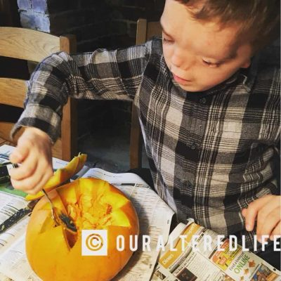Harry hollowing out his own pumpkin