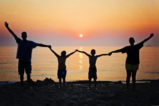 childrens mental health a family stand with their back to the sun, arms raised in the air together