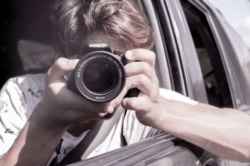 childrens mental health - a boy leans out of a car window to take a photograph with a camera which is facing us