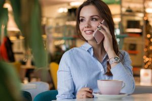 A woman is sitting drinking coffee and smiling on the phone with a friend