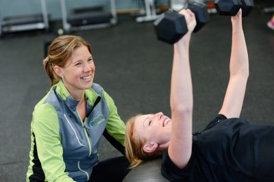 A woman lifts weights at the gym with a trainer watching on